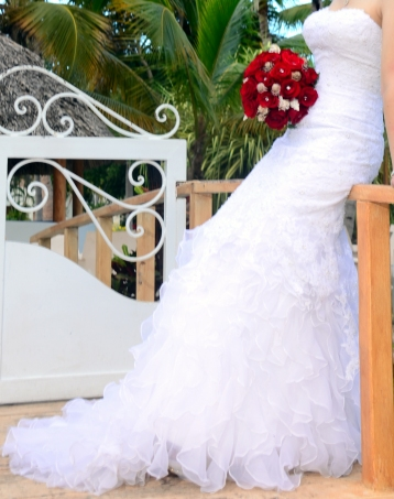 Bridal gown with red rose bouquet