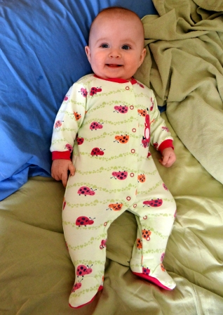 Smiling infant in adult bed.