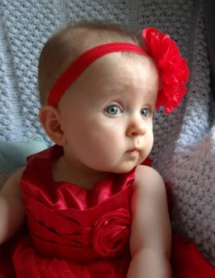 Baby girl poses in a red dress and flower headband