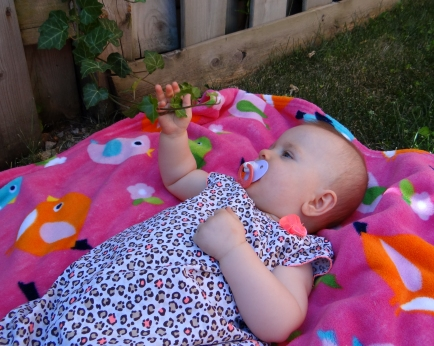 Baby outdoors holding ivy