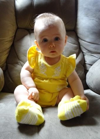 Infant wearing a yellow outfit sitting unassisted