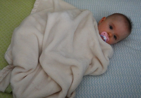 Baby bundled in a fuzzy blanket in a crib
