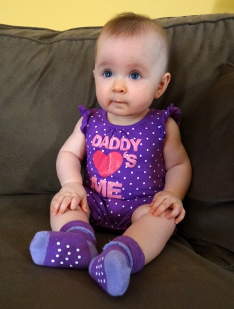Cute baby girl sitting on a couch
