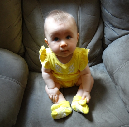 Adorable baby girl in a yellow outfit.