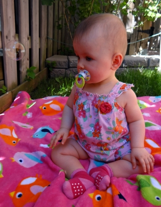 Baby girl having outdoor fun with bubbles