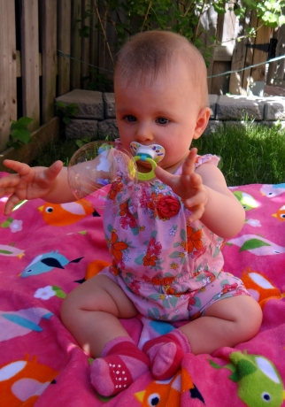 Baby catching a soap bubble.