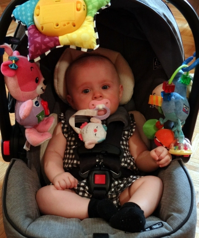 Baby in a car carrier with toys