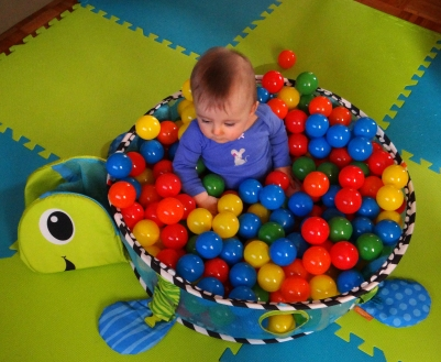 Baby in the Infantino Grow-With-Me Activity Gym & Ball Pit