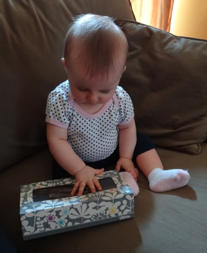 Baby playing with a tissue box