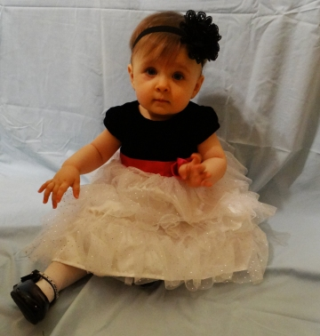 Baby in a party dress, headband, and shoes.