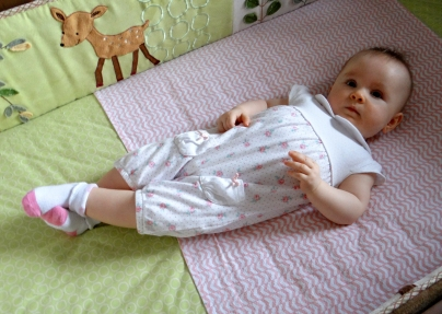 Baby in a crib with legs crossed