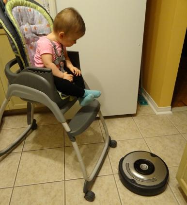Baby watches Roomba vacuum