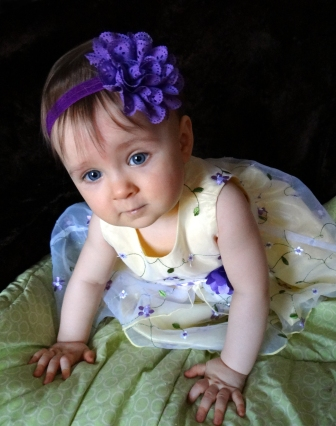 Baby dressed up in yellow dress with purple flowers