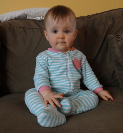Baby girl sitting on a couch independently