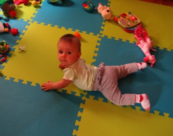 Baby doing exercises to learn how to crawl