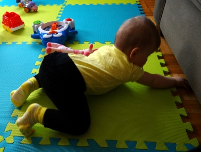 Baby reaching underneath the couch.