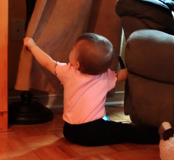 Baby playing with a curtain