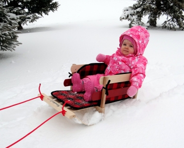 Baby going sledding in the winter