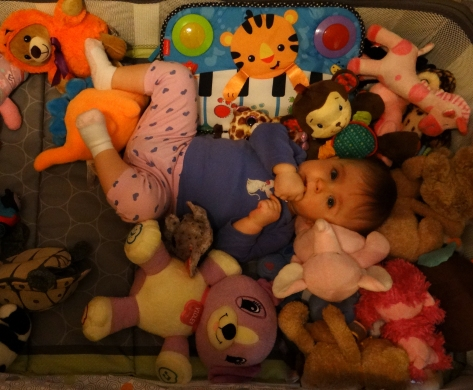 baby surrounded by toys and stuffed animals