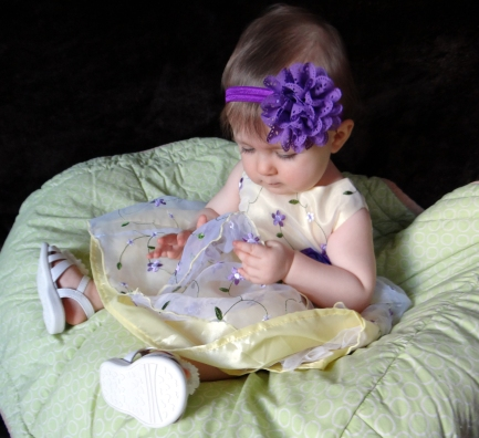Baby examining her dress