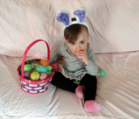 Baby dressed as the Easter Bunny with an Easter basket full of eggs.