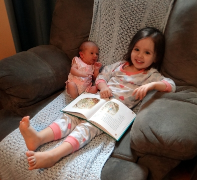 Peachy reading to her baby sister