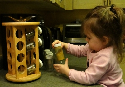 Toddler playing with a spice rack